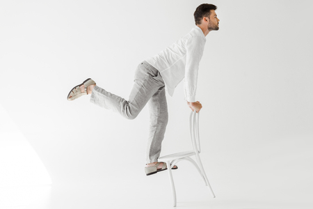 profile of male model in linen clothes balancing on chair isolated on grey background Reklamní fotografie