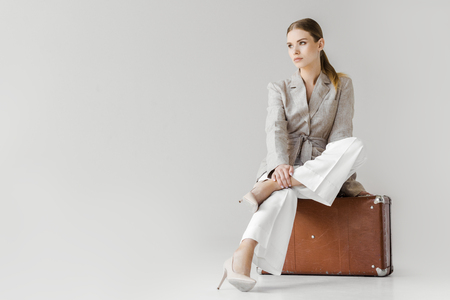 stylish woman in linen jacket sitting on vintage suitcase and looking away isolated on grey background