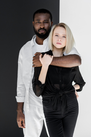 african american boyfriend hugging blonde girlfriend near black and white wall