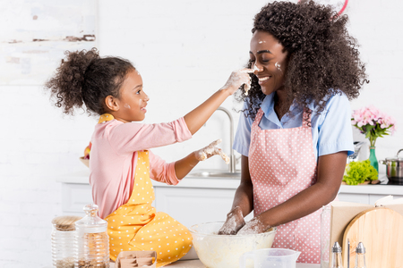 african american mother and daughter having fun while making dough on kitchen Stock Photo - 106868202