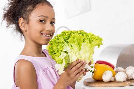 smiling african american child holding green fresh lettuce in kitchen Stock Photo
