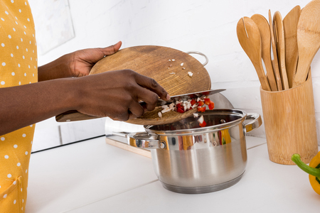 partial view of african american woman putting ingredientes into saucepan on kitchen