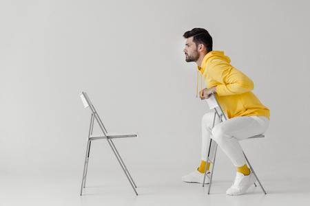 Élégant jeune homme en sweat à capuche jaune assis sur une chaise devant une autre chaise sur blanc