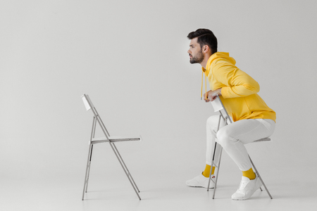 stylish young man in yellow hoodie sitting on chair in front of another chair on white