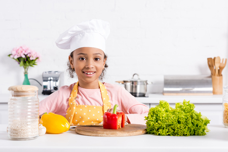 smiling african american kid in apron and chef hat preparing vegetables on kitchen