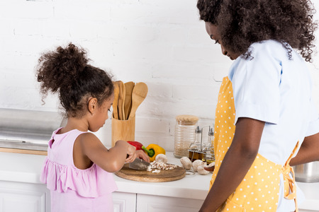 african american mom and daughter cutting vegetables on kitchen Imagens