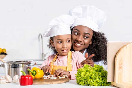 african american mother and daughter in chef hats cutting vegetables and looking into cookbook Stock Photo