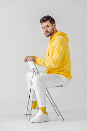side view of handsome young man in yellow hoodie sitting on chair on white Banque d'images - 106871332