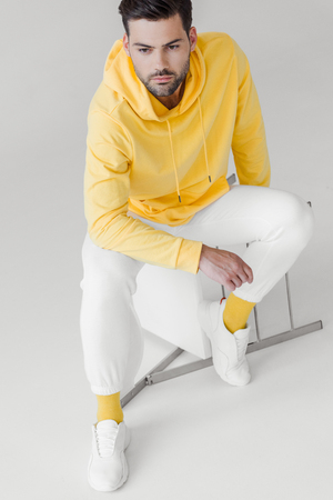 high angle view of handsome young man in yellow hoodie sitting on flipped chair on white