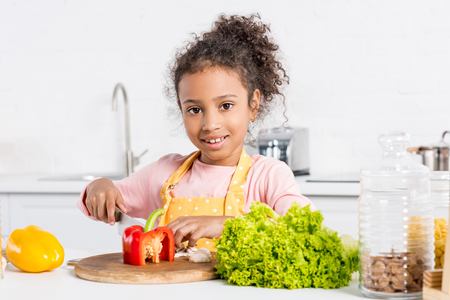 adorable african american kid in apron cutting bell peppers and lettuce on wooden board in kitchen Stock Photo