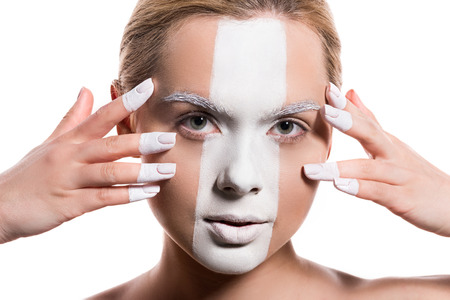 attractive woman with white paint on face and fingers looking at camera isolated on white