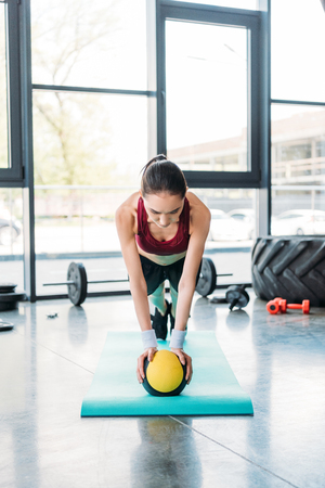 young asian sportswoman balancing on ball on fitness mat at gym