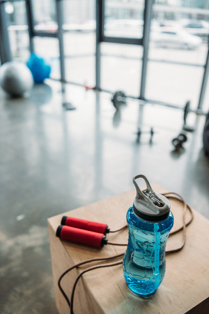 closeup view of jump rope and bottle of water on wooden box at gym Stockfoto