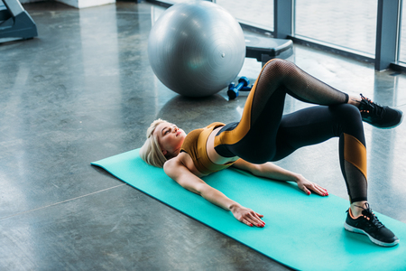 young athletic woman stretching on fitness mat at gym