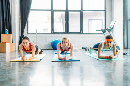 front view of multiethnic female athletes doing plank on fitness mats at gym