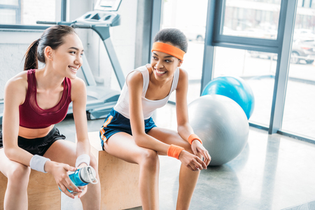 smiling african american sportswoman and asian sportswoman with bottle of water sitting on wooden boxes at gym