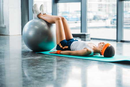 side view of african american sportswoman on mat exercising with fitness ball at gym Reklamní fotografie