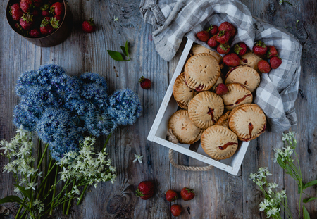 top view of tasty cookies with strawberries in tray, flowers on wooden table