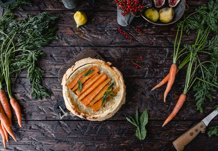 top view of tasty pie with carrots and herbs on wooden table