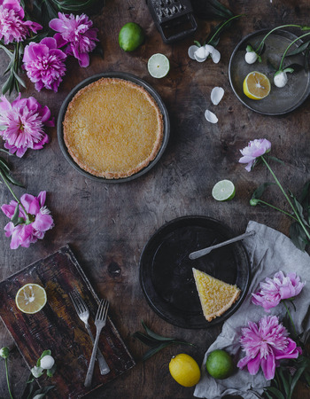 top view of tasty lemon pie and peonies on wooden table