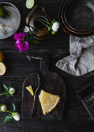 elevated view of piece of tasty lemon pie and flowers on wooden table Фото со стока - 108009322