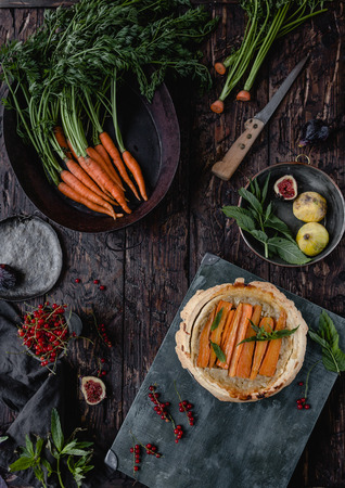 elevated view of tasty pie with carrots, figs and currants on wooden table