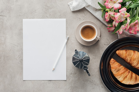 top view of cup of coffee with blank paper, croissants and alstroemeria bouquet on concrete surface 版權商用圖片
