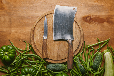 Cleaver and smaller knife on cutting board with green vegetables on wooden table