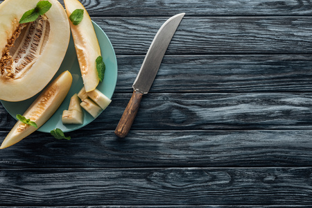 top view of sweet ripe melon with mint on plate and knife on wooden surface