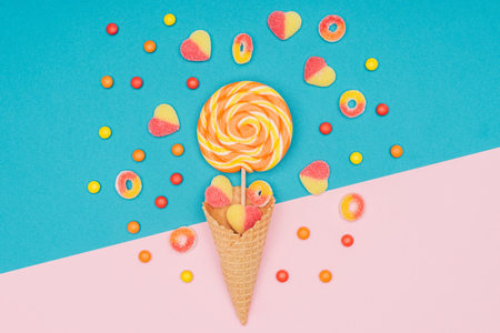 top view of jelly candies, lollipop and waffle cone on blue and pink surface Фото со стока