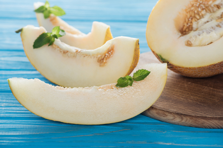 close-up view of sliced sweet ripe melon with mint on blue wooden surface