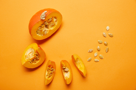 top view of ripe sliced pumpkin with seeds on orange background