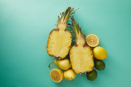 elevated view of cut pineapple, pears and lemons on turquoise surface Stock Photo
