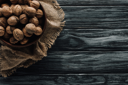 walnuts in wooden bowl on sackcloth on dark wooden surface Zdjęcie Seryjne