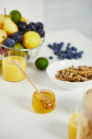 close up view of honey, fresh fruits and glass of juice for breakfast on white surface