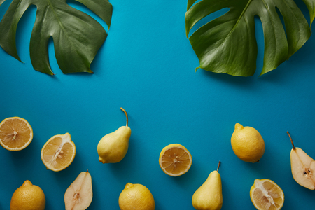 top view of palm tree leaves, pears and lemons on blue surface