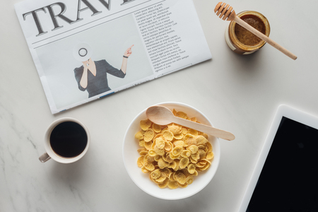 top view of breakfast of cereal and coffee on white marble surface with newspaper and table