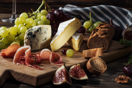 different types of cheeses, prosciutto and grapes on cutting board