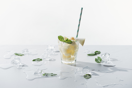 delicious summer drink with mint and melon in glass and melted ice cubes on white