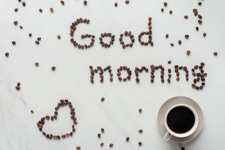 top view of cup of coffee and good morning lettering made of coffee beans on white marble