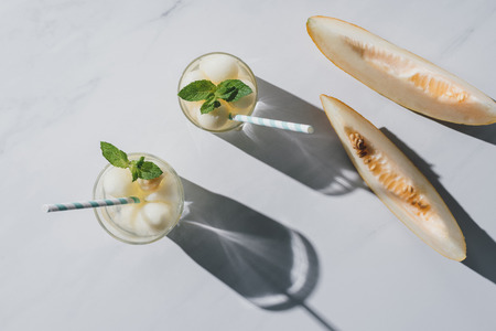 top view of refreshing beverage with melon and mint in glasses and slices of ripe melon on white