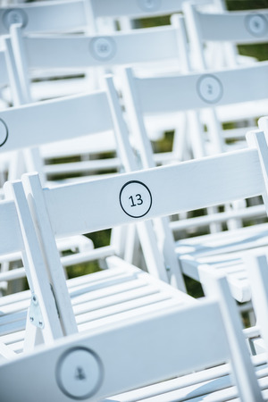 close-up view of empty white chairs with numbers on green lawn