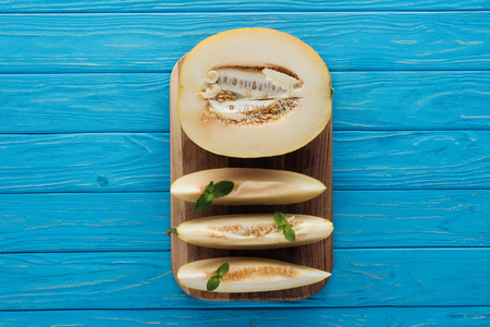 top view of sweet ripe sliced melon on cutting board on blue wooden surface Stock Photo