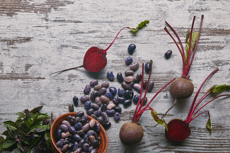 Raw beetroots and haricot beans on rustic wooden table Фото со стока