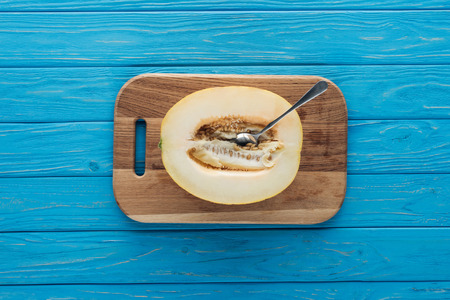 top view of sweet ripe melon with spoon on cutting board on blue wooden surface