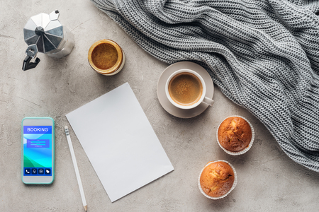 top view of cup of coffee with muffins, blank paper and smartphone with booking app on screen on concrete surface with knitted wool drapery