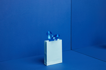close up view of paper shopping bag on blue backdrop