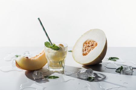 summer drink with mint and melon in glass, melted ice cubes and sweet ripe melon on white