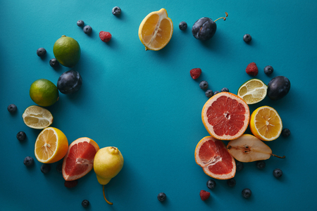 top view of organic ripe fruits and berries on blue surface Stock Photo