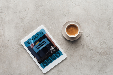 top view of cup of coffee and tablet with booking app on screen on concrete surface